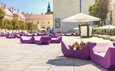 Sonnenliegen in Stadt. Frau liegt in Sonnenliege und ließt Buch unter Sonnenschirm. Sun lounger in City. Woman reading a book in sun lounger under sunshade.