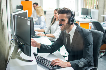 Smiling male customer support operator agent with hands-free device working in call center