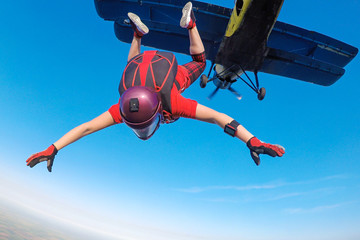 Skydiver in red jumping out of the plane