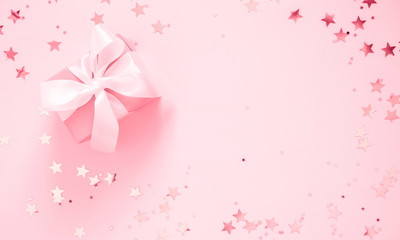 gift with satin bow and shining stars on light pink pastel background