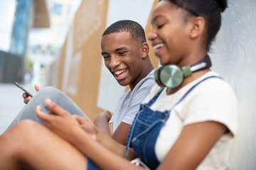 Teenagers socialising outdoors in city looking at smartphone