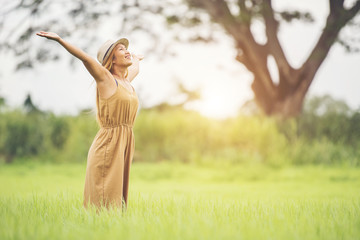 Young woman standing in grass field raising hands in the air.