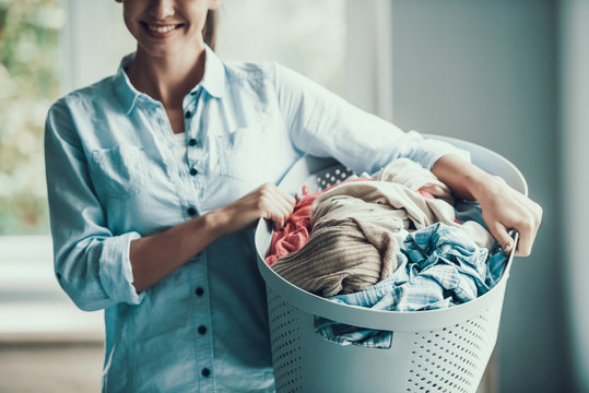 Young Smiling Woman holds Basket of Clean Clothes