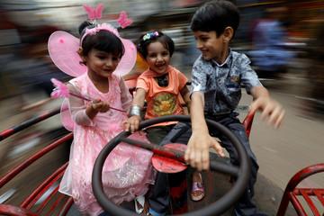Children ride a merry-go-round, during Eid al-Adha celebrations in Karachi