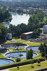 Sewage water treatment plant with storage tanks, aerial view, sunny summer day