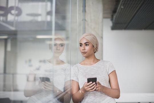 Muslim businesswoman using a smartphone in an office