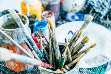 Pennelli d'artista e sfondo di barattoli di colore