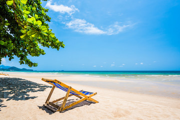 Tropical tree and beach chair at white sand beach and blue sea