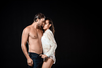 sexy couple with wet hair posing isolated on black