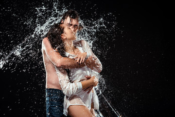 portrait of seductive couple with water splash isolated on black