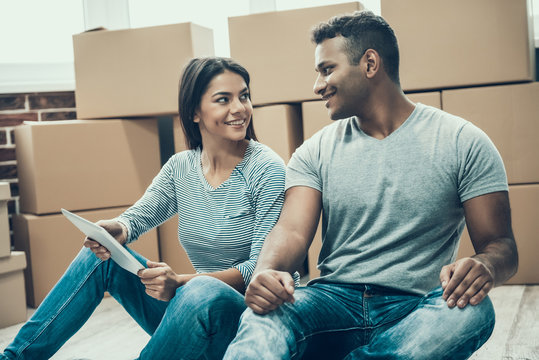 Young Smiling Couple Resting after Packing Boxes