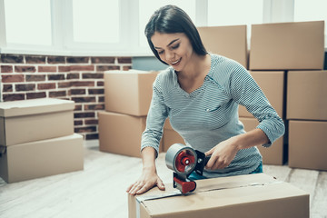 Young Smiling Woman Packing Cardboard Box at Home