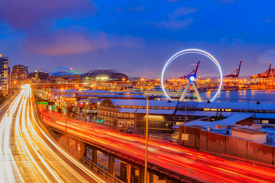 Seattle waterfront at sunset with Great Wheel and trail lights