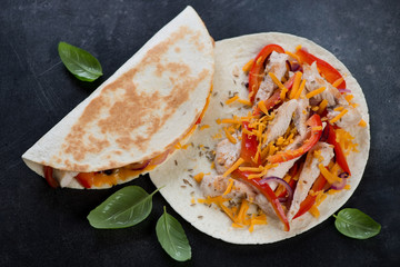 Quesadillas with grilled chicken meat, vegetables and cheddar cheese, high angle view on a dark metal background