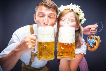 Oktoberfest, Frau und mann in Bayerischer Tracht mit Bier Krügen