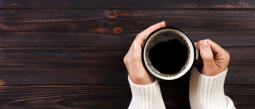 Lonely woman drinking coffee in the morning, top view of female hands holding cup of hot beverage on wooden desk. Banner