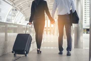 Asian Business man and woman  Dragging suitcase luggage bag,walking to passenger boarding in Airport,travel to work. Couple of love wearing black suit pull trolley bag. Business travel concept
