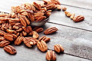 Pecan nuts on a rustic wooden table and pecan nuts in bowl
