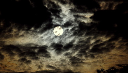Księżyc na tle ciemnego, nocnego, lekko zachmurzonego nieba