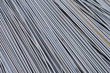 Stack of heavy metal reinforcement bars with periodic profile texture. Close up steel construction armature. Abstract industrial background concept. Copy space.
