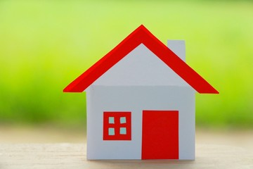 Paper cut of house red roof on green background.