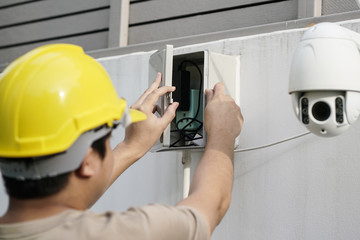 Close Up Of Male Technician Fixing CCTV Camera On Wall