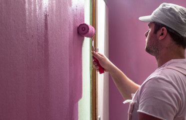 Young man is painting wall with roller