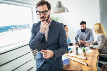 Portrait of young businessman using digital tablet while colleague in background