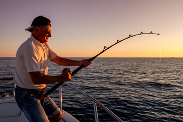 Printed kitchen splashbacks Fishing angler fishing on the sea from the boat at sunset