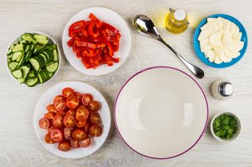 Empty bowl, chopped ingredients for vegetable salad, mozzarella, salt, vegetable oil
