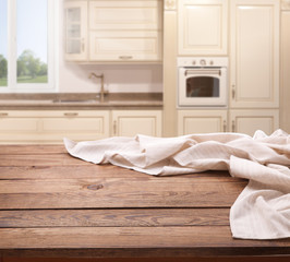 Empty wooden table with white tablecloth near the window in kitchen. White Napkin close up top view mock up. Kitchen rustic background.