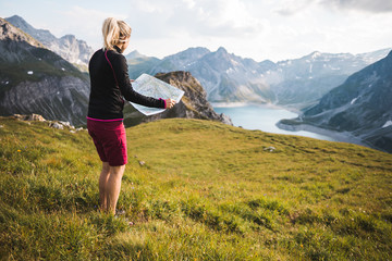 Adventurous Outdoor Girl Exploring great Alpine Mountains with a topographic Map