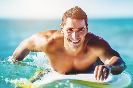 Handsome young surfer floating in blue water