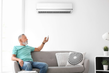 Mature man operating air conditioner while sitting on sofa at home