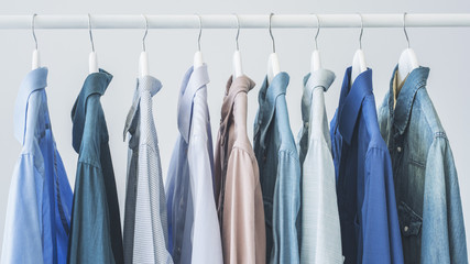 Assorted blue shirts hanging on wooden hangers
