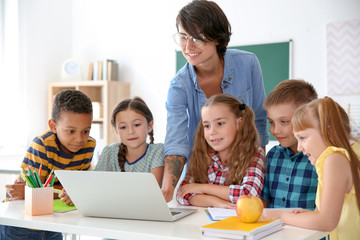 Female teacher helping children with assignment at school