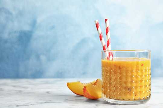 Tasty peach smoothie in glass and fresh fruit on table