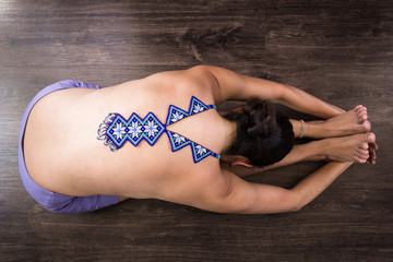 Top less woman on seated forward bend pose with huichol blue necklace on naked back and hands holding feet. Female yogi on paschimottanasana. Fashion design, Mexican handcraft, decoration art concepts