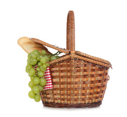Wicker basket for picnic filled with food on white background