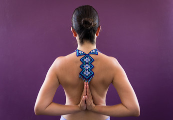 Top less woman on pashchima namaskarasana over purple wall with huichol necklace on naked back. Female yogi on reverse prayer pose with traditional handcraft from Mexico. Penguin pose, fashion concept