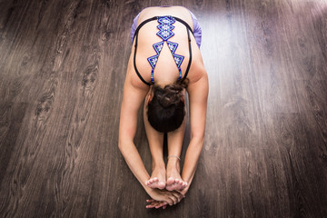 Flexible woman on black bra poses with huichol blue necklace on back. Female yogi on paschimottanasana pose on wood planks floor. Lady on foward bend asana from top. Mexican traditional handcraft