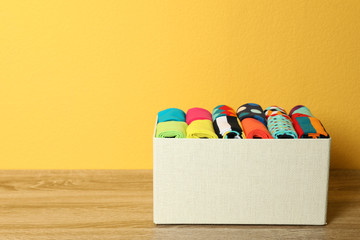 Fototapete - Box with colorful socks on wooden table against color background