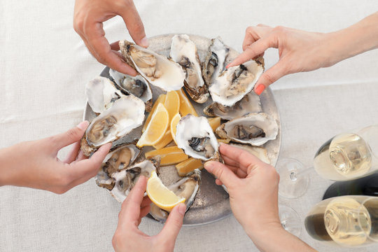 Top view of people with fresh oysters at table, focus on hands
