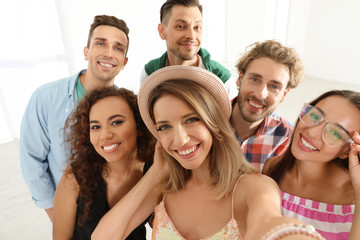 Group of happy young people taking selfie indoors