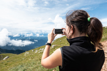 Young woman taking a picture with phone on mountain Sciliar