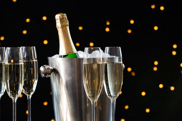 Glasses with champagne and bottle in bucket against blurred lights