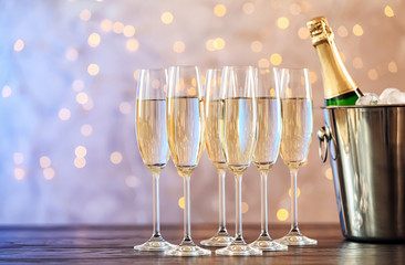 Glasses with champagne and bottle in bucket on table against blurred lights