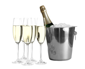 Glasses with champagne and bottle in bucket on white background
