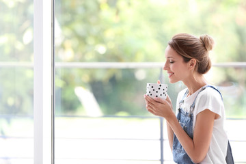 Young woman with cup of aromatic coffee near window at home