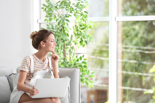 Young woman with laptop sitting on sofa near window at home